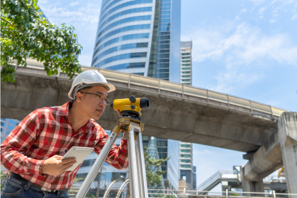 a surveyor using a Theodolite at a construction site to measure the angle