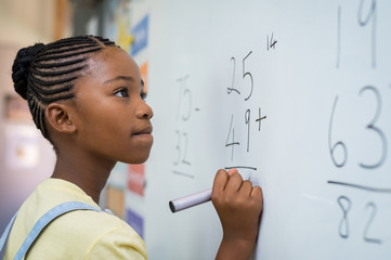 A girl trying to solve math problem given by the teacher