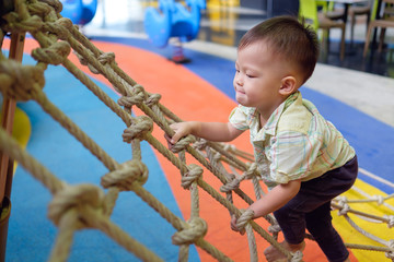 A child climbing the rope in order to learn balancing