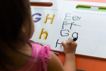 Kids learning to write alphabets