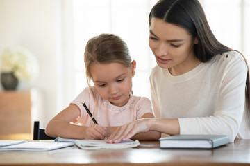 A parent helping her child to learn alphabets