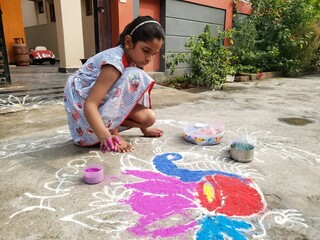 Kid drawing rangoli