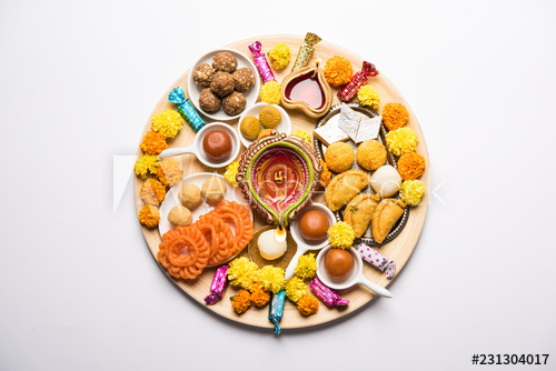 Diwali sweets arranged in a plate with diya and flowers