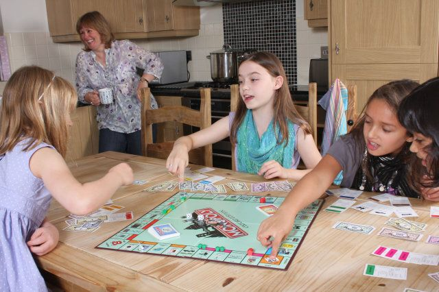 Children playing indoor games such as monopoly