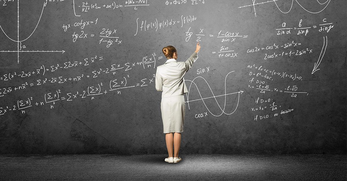 Teacher solving math equation on black board