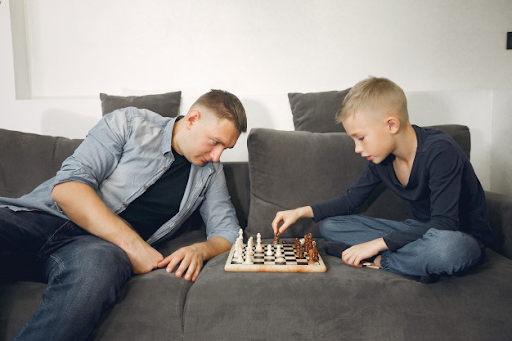 Kid playing board games with his dad