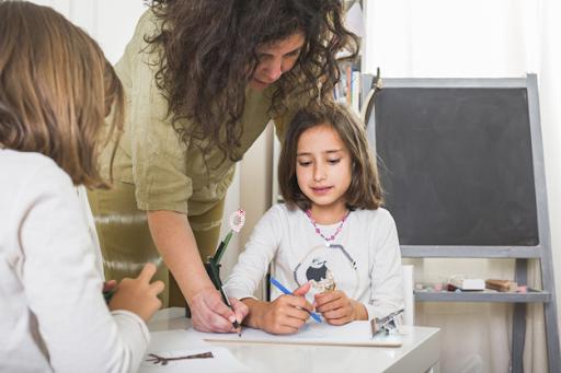Teacher having patience towards each kid and correcting mistakes