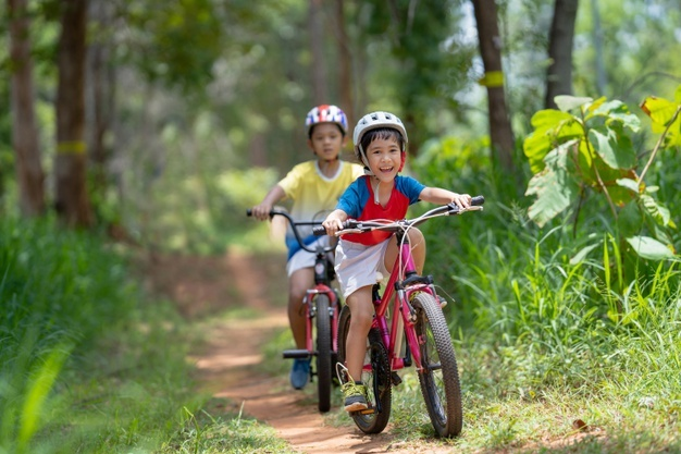 Asian children are happy bicycling.