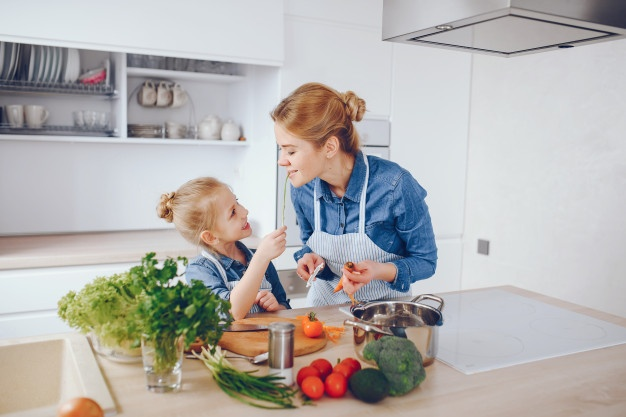 Beautiful mother is teaching her child to prepare fresh vegetable salad at home