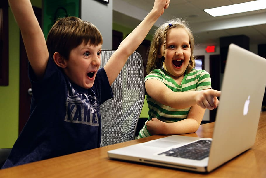 Boy and Girl getting excited by looking at the grey macbook screen