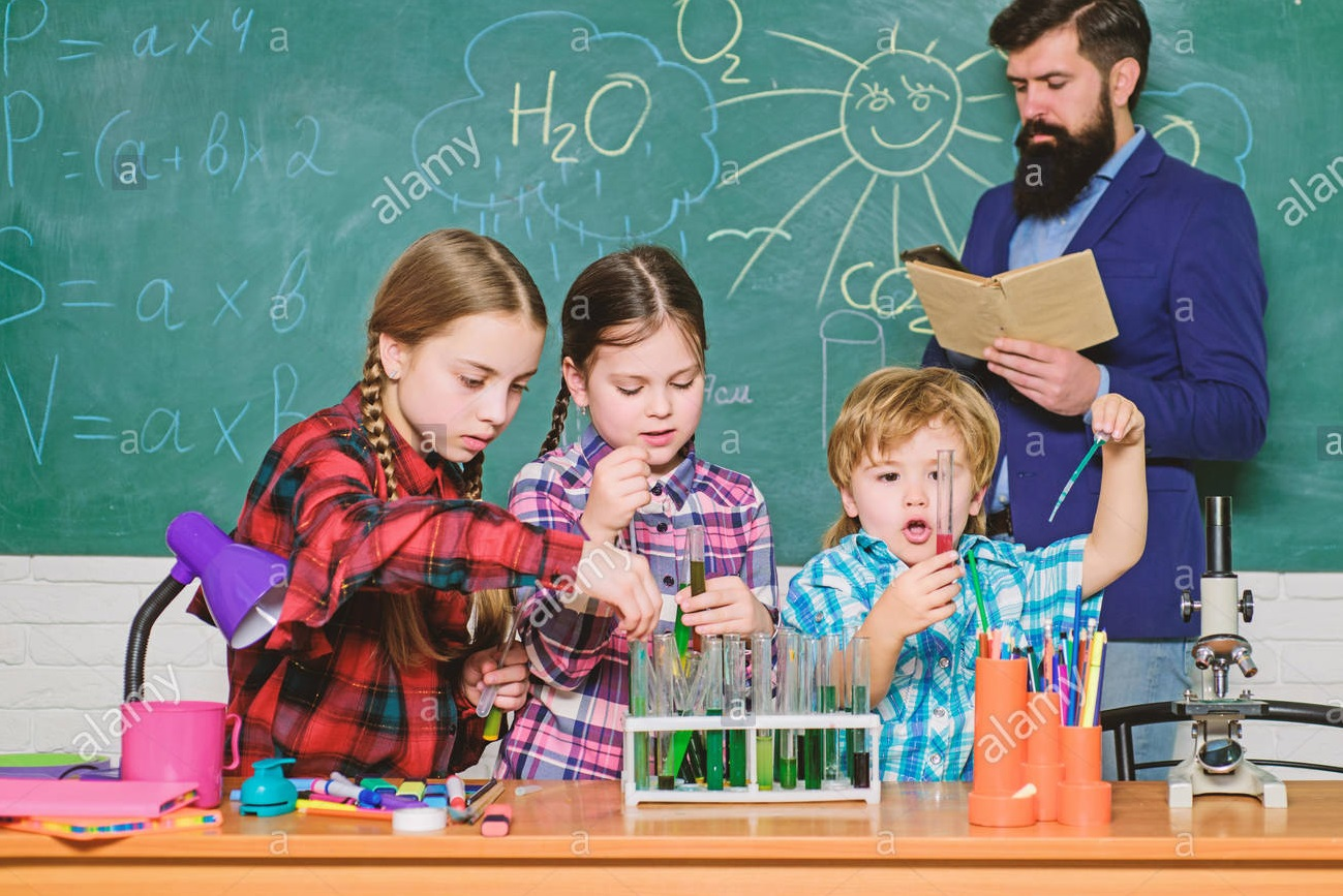 Kids performing chemical activities under teacher's supervision