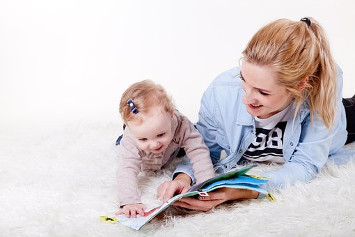 mother and child reading from a book at home
