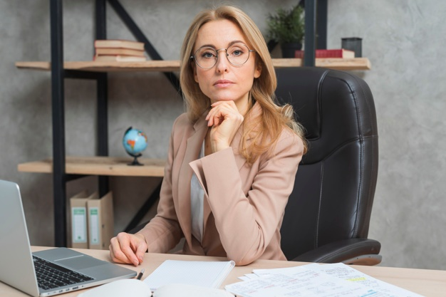 Confident young businesswoman sitting at workplace with laptop in the office