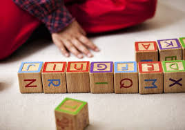 Kid rearranging alphabets in blocks
