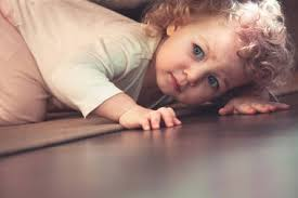 A baby peeping under a table