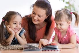 mother reading from a book to her daughters