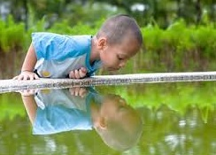 child looking at his reflection in water