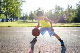 A kid dribbling basketball on court
