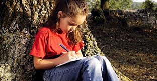 Kid writing a diary sitting under a tree