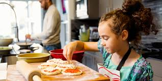 A kid adding toppings to pizza