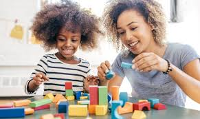 Mother playing building blocks with daughter