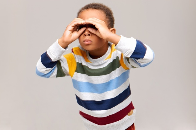 Isolated shot of curious american boy making gesture with both hands near eyes and looking through holes as if using binoculars, searching something at distance. childhood and fun concept