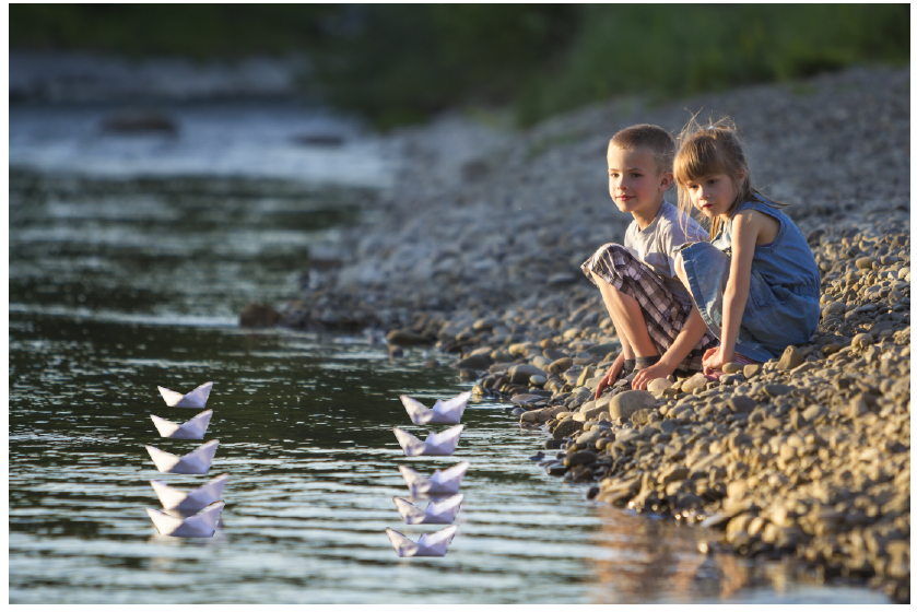two children floating paper boats in a river