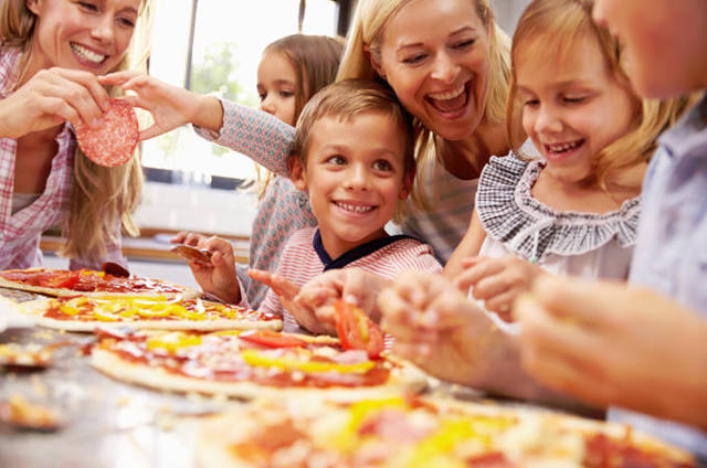 Children adding topping to pizza