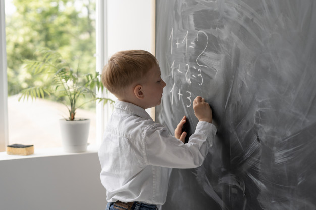 student becomes teacher in the classroom writes math examples on the blackboard,