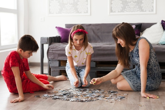 Mother playing jigsaw puzzle with her children at home