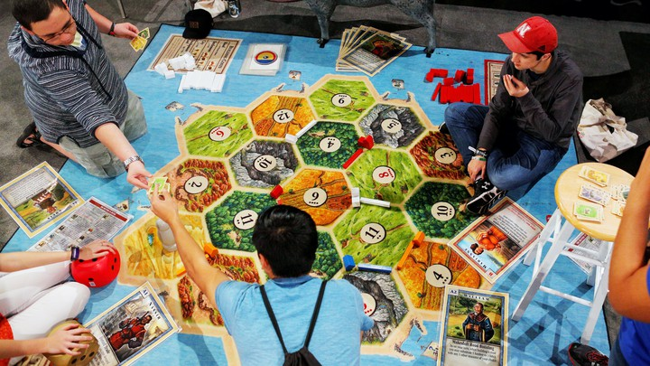 Teenagers playing a Complex Board Game, Catan
