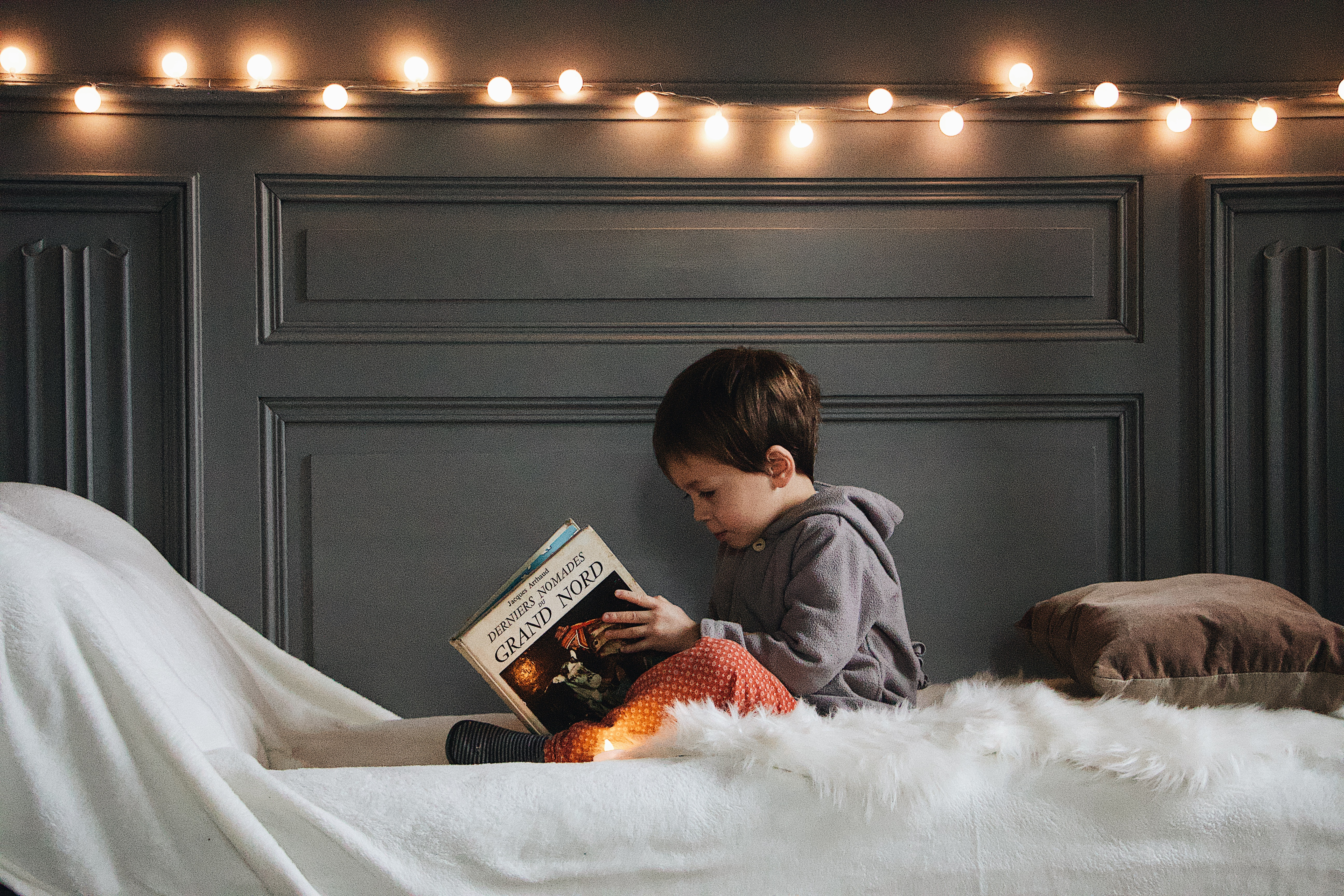 A kid reading book on his bed