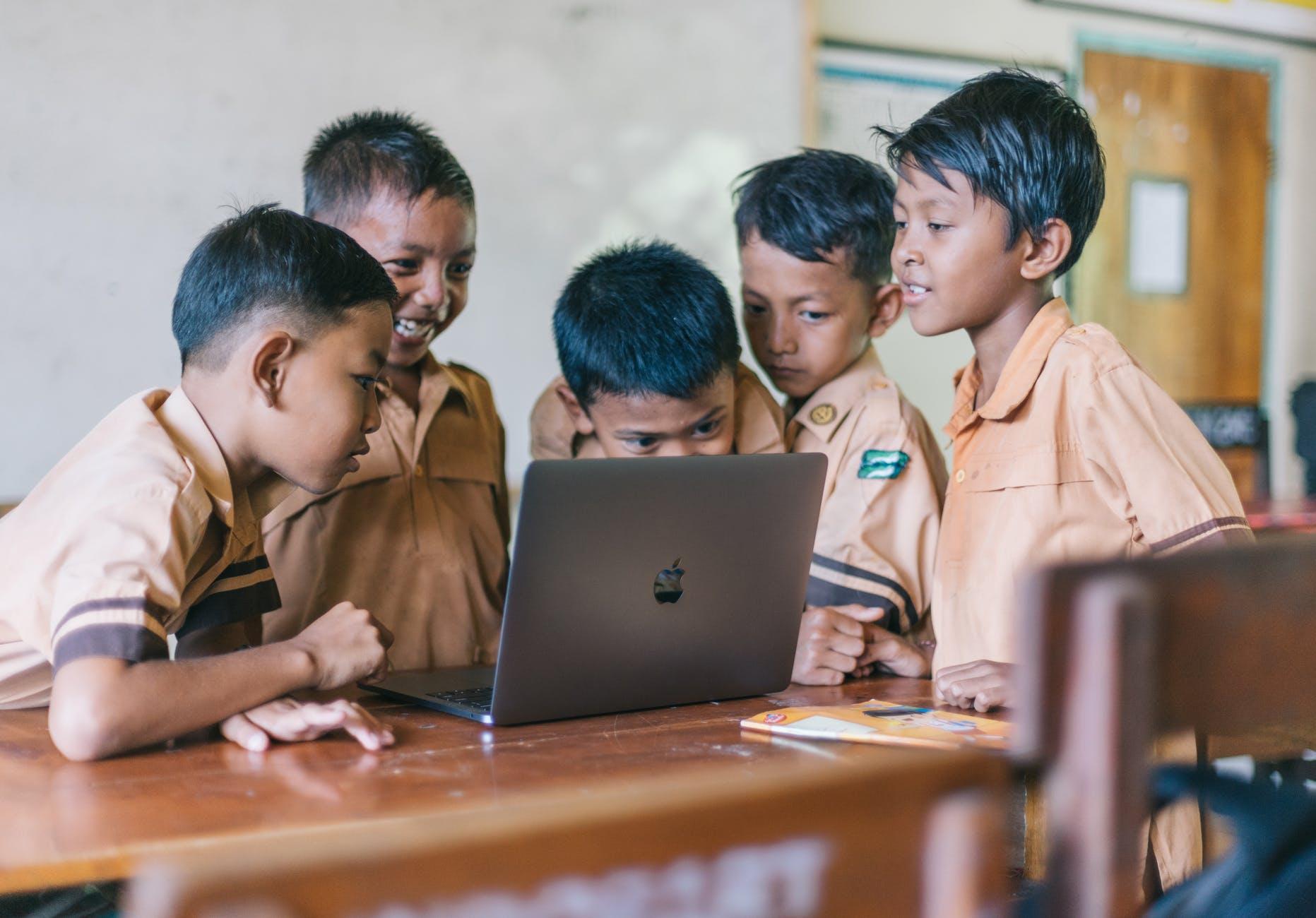 Kids smiling by looking at grey macbook