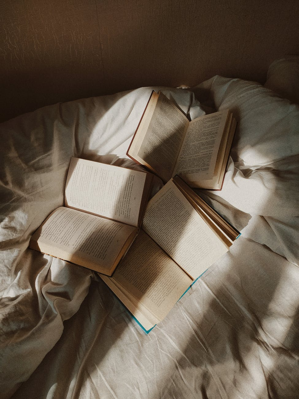 Opened books placed on disheveled bed.