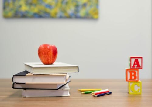 Montessori school for ages 3-6: book, apple, pencils, letters