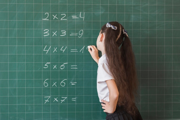 Pupil making math exercise on chalkboard