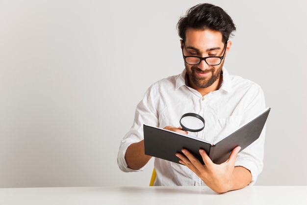 Smiley young man reading with loupe