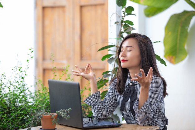 Smiling businesswoman shows gestures to meditate