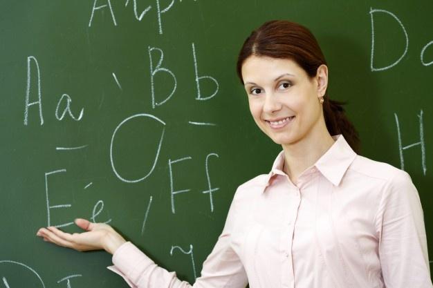 Smiling teacher explaining english grammar with blackboard background
