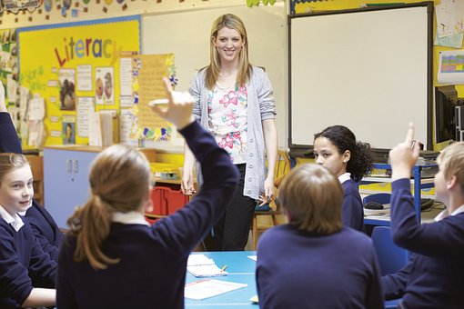 Teacher having a question and answer session in classroom and students raising hands to answer