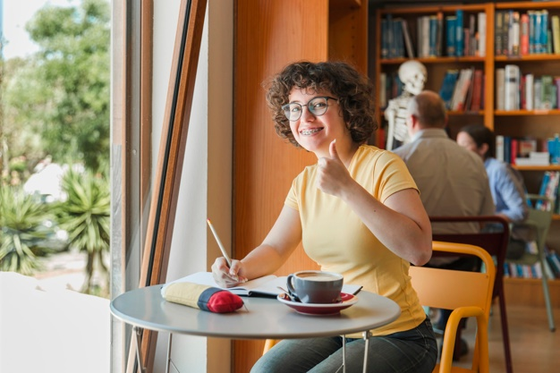 Teenager studying and gesturing thumb-up