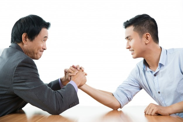 Two business men arm wrestling aggressively