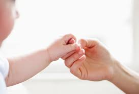 A child trying to connect with her mother by holding her hand.
