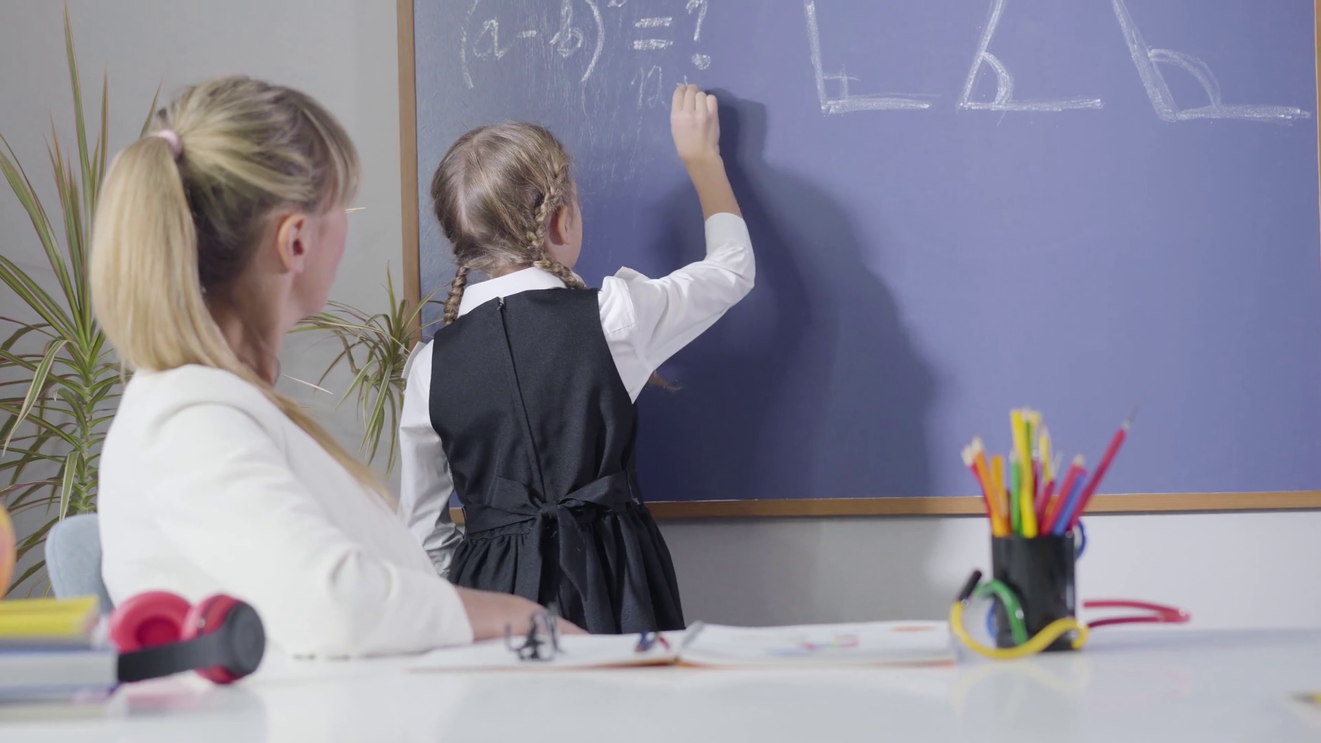 A child solving word problems in-front of teacher with the help of diagrams