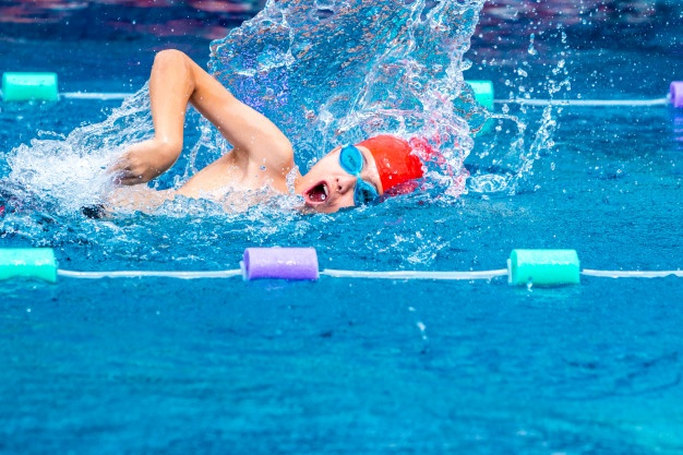 Young boy swimmer practicing his freestyle stroke in a local swimming pool