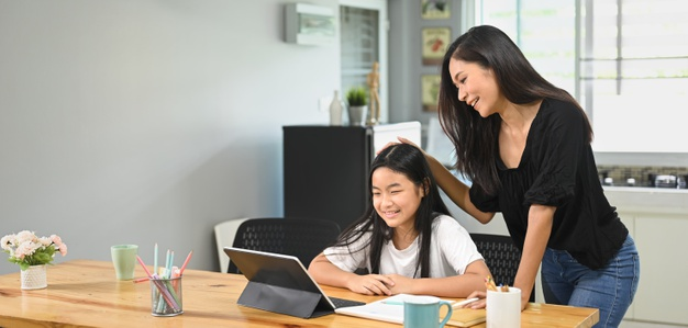 A young mother is teaching a daughter to do homework at the wooden table taking care of important aspects of her education